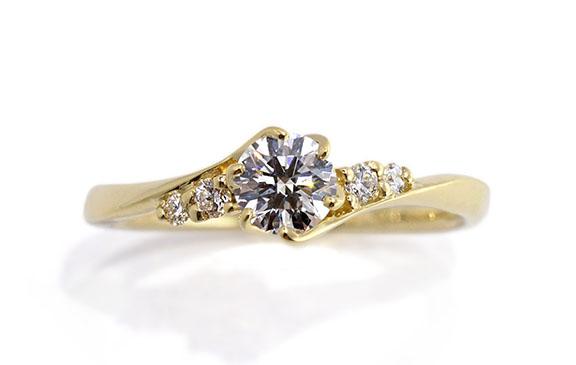 5石のダイヤが流れにつつまれる婚約指輪
